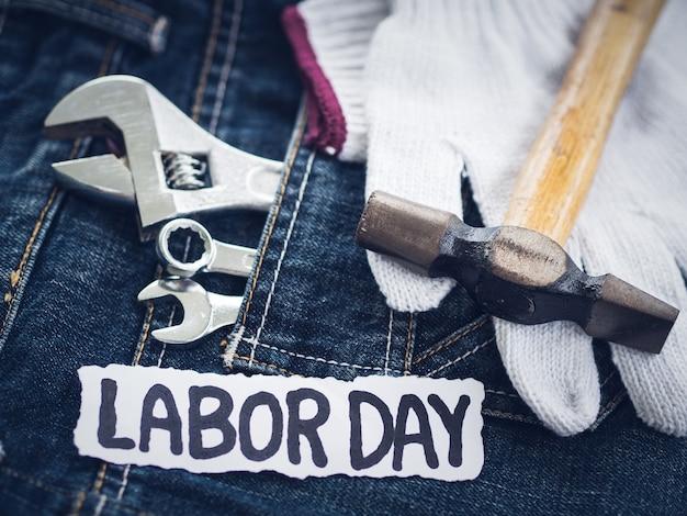 Werktagshintergrundkonzept - viele handlichen werkzeuge auf jeanshintergrund