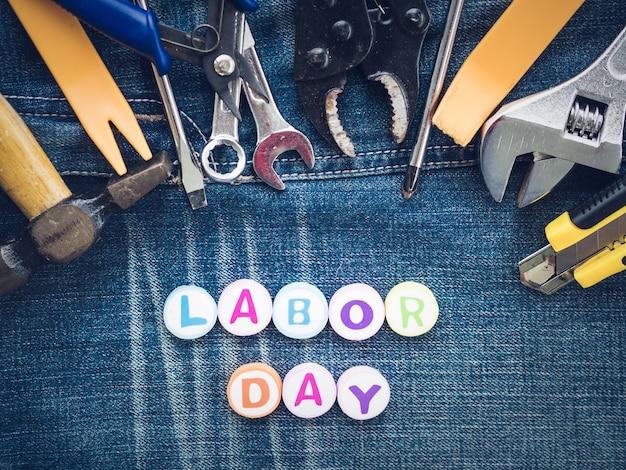 Werktagshintergrundkonzept - viele handlichen werkzeuge mit werktag simsen auf jeanshintergrund
