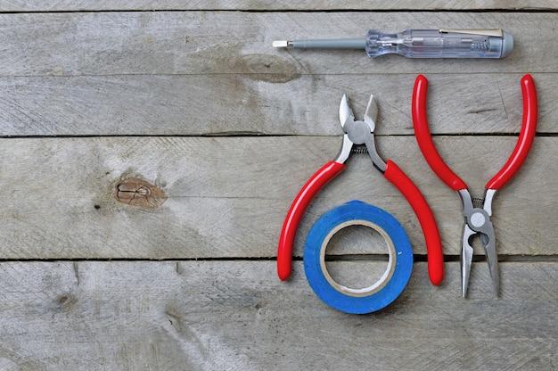 Werkzeug für reparaturelektriker auf einem hölzernen hintergrund. draufsicht. platz für text.