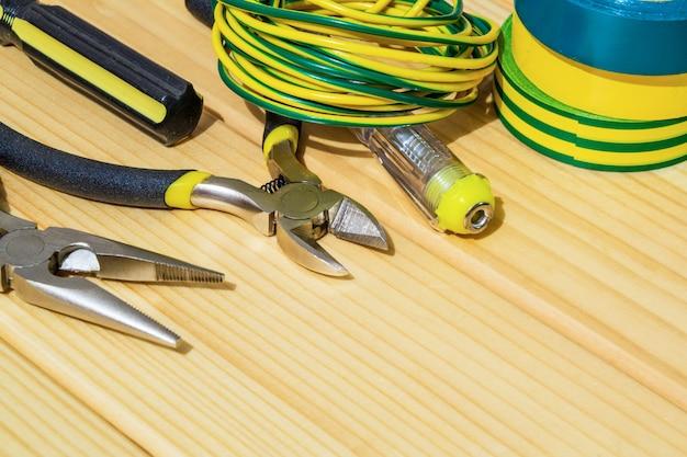 Werkzeug und ersatzteile für elektriker auf holzbrettern