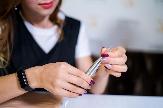 Werkzeug zum microblading in den händen des tätowierers. permanent make-up an.