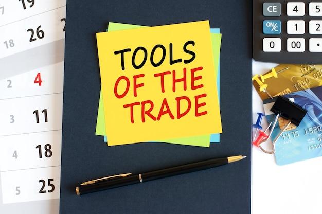 Werkzeuge des handelstextes auf gelber papierquadratform. notepad rechner kreditkarten stift briefpapier auf dem desktop selektiver fokus