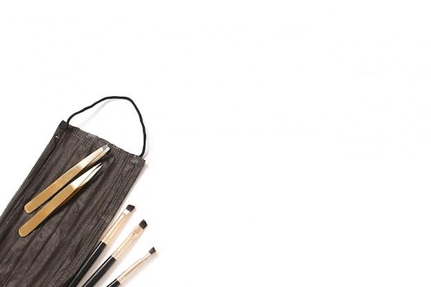 Werkzeuge für die augenbrauenformung. maske, pinzette, pinsel. draufsicht, platz für text. weißer hintergrund.