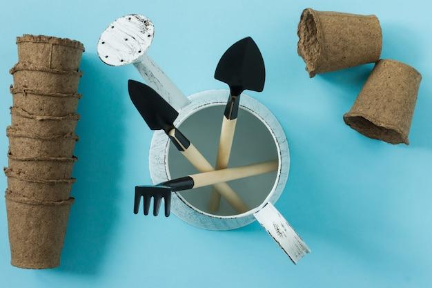 Werkzeuge für die gartenarbeit zu hause. gartengeräte für topfpflanzen: schaufel, gießkanne und rechen. ansicht von oben. flatlay auf blauem hintergrund.