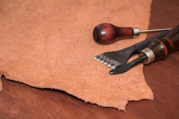 Werkzeuge für die lederherstellung und braune lederstücke. herstellung von lederwaren.