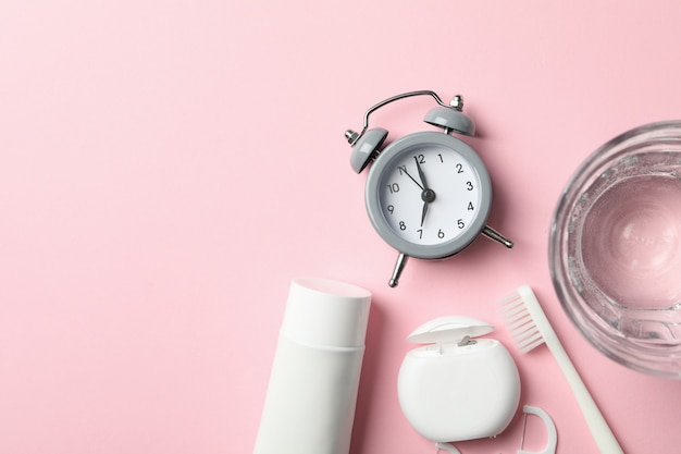 Werkzeuge für die zahnpflege auf rosa oberfläche