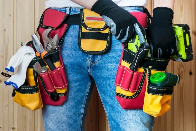 Werkzeuge im gurt für werkzeuge. der erbauer hält einen elektroschrauber