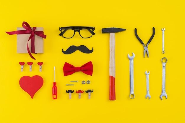 Werkzeuge mit geschenkbox, papierschnurrbart und herz