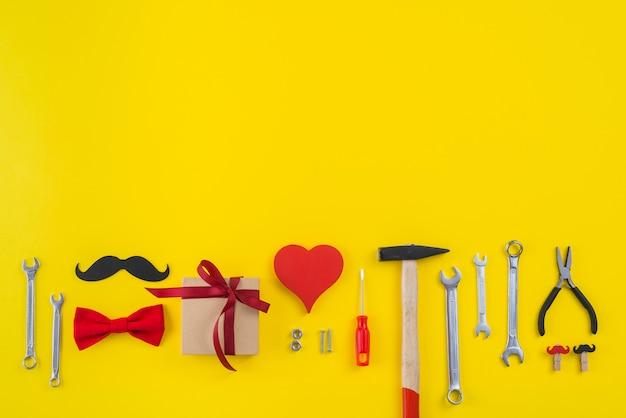 Werkzeuge mit geschenkbox, papierschnurrbart und rotem herzen