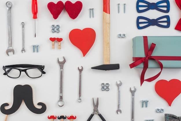 Werkzeuge mit geschenkbox, schwarzem schnurrbart und roten herzen