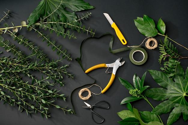 Werkzeuge und accessoires, die ein florist benötigt, um einen blumenstrauß zusammenzustellen