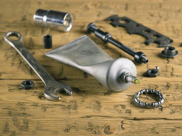Werkzeuge und fett für fahrradreparatur auf dem holztisch.