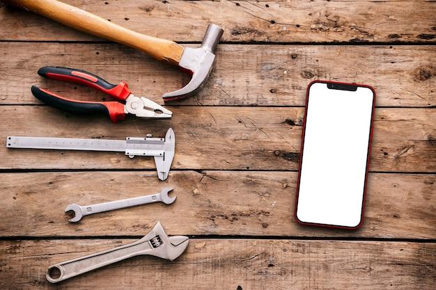 Werkzeuge und handy auf rustikalem tisch