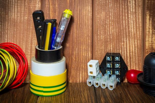 Werkzeuge und zubehör auf einem vintage-holzhintergrund, der in elektroinstallationen verwendet wird