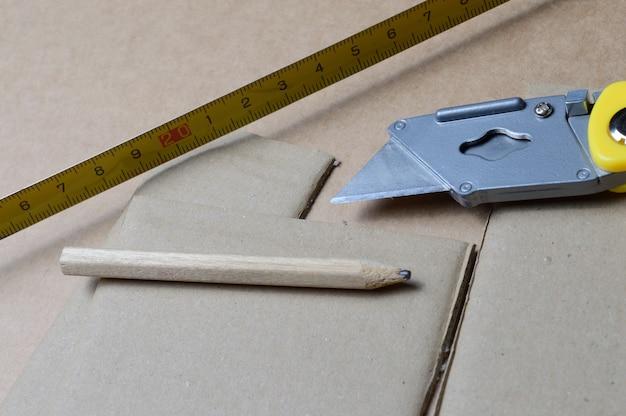 Werkzeuge zum arbeiten mit karton, der auf einem tisch mit kartonresten ausgelegt ist.
