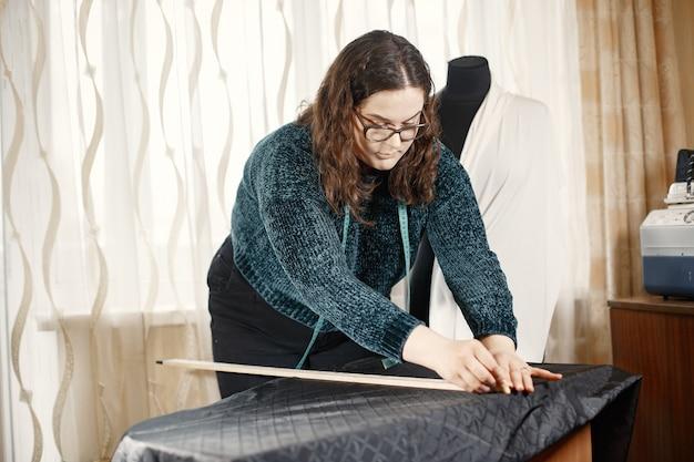 Werkzeuge zum nähen von kleidung. frau und brille. näherin mit einem zentimeter für kleidung