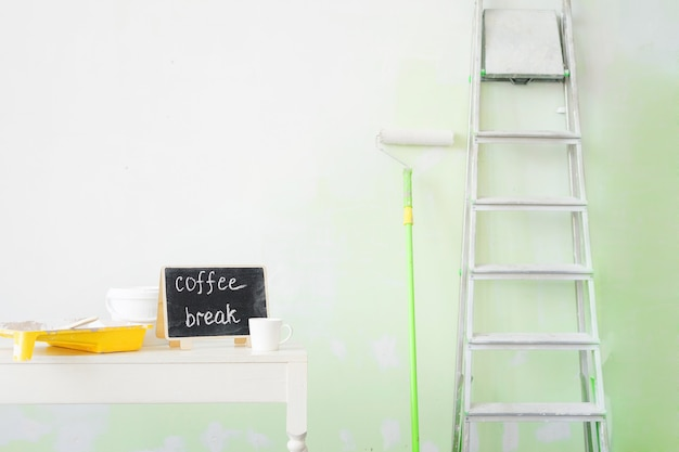 Werkzeuge zum streichen von wänden und eine tasse kaffee.