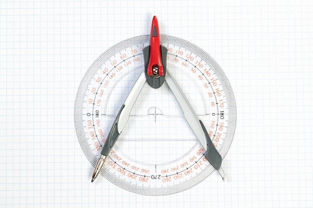 Werkzeuge zum zeichnen von kompass und winkelmesser. an einer weißen wand.