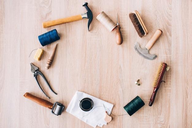 Werkzeuge zur herstellung von lederwaren. werkzeuge auf einem holztisch ausgelegt. hammer, pinsel, ahle, messer, faden, seil auf dem tisch. manuelle herstellung von ledertaschen.