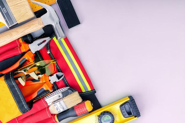 Werkzeuggürtel mit werkzeugen auf grauem hintergrund
