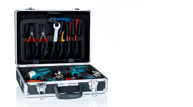 Werkzeugkasten isoliert auf weißem hintergrund. schwarzer werkzeugkasten mit werkzeugen. zange, schraubenschlüssel oder schraubenschlüssel, schraubendreher, cutter und akku-bohrer im werkzeugkoffer.