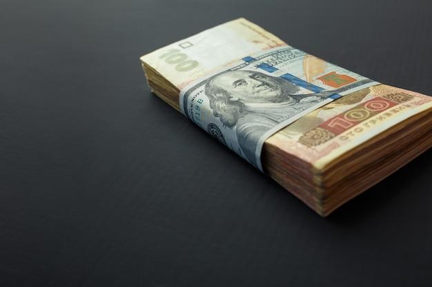 Wert der ukrainischen griwna und us-dollar. eine packung ukrainischer griwna wickelte einen hundert-dollar-schein ein