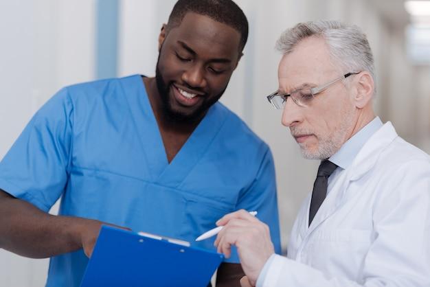 Wertschätzung ihrer erfahrung. neugieriger glücklicher afroamerikanerpraktikant, der in der klinik steht, ordner hält und auf den rat des erfahrenen arztes hört