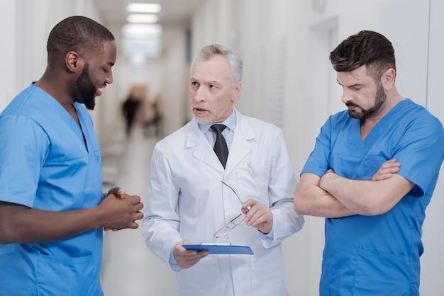 Wertvolle erfahrungen teilen. konzentrierte erfahrene ältere praktizierende, die in der klinik stehen, den ordner halten und sich mit jungen kollegen unterhalten