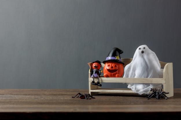 Wesentlicher dekorationszusatz des glücklichen halloween-festivalkonzepthintergrundes vielzahl der einzelteile die geisthandgemachten und jack-o-laternenkürbise auf modernem rustikalem büro-studiowand des hölzernen holzes zu hause.