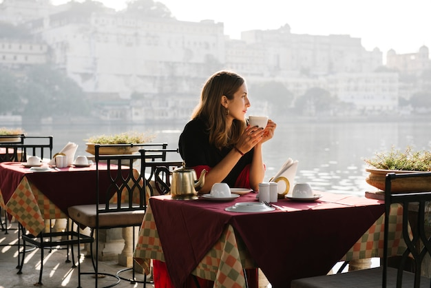 Westfrau, die eine teatime an einem café in udaipur hat