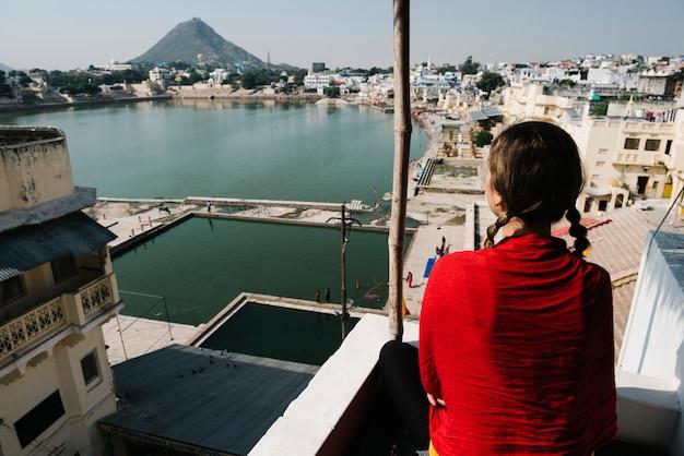Westliche frau, die eine ansicht von pushkar see in rajasthan genießt
