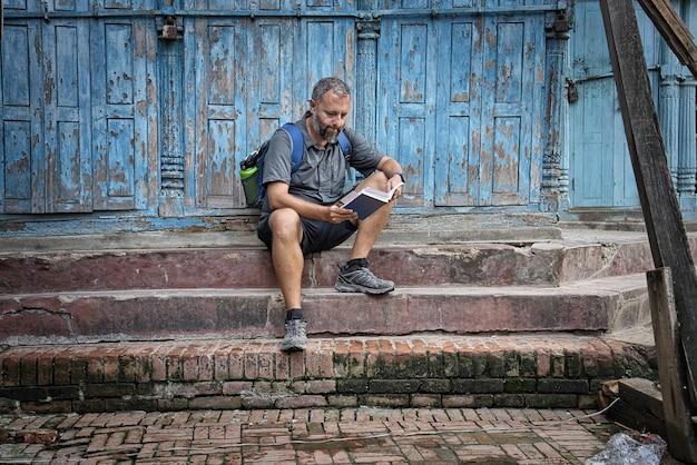 Westlicher junger mann mit dem rucksack und kurzen jeans, die auf braunen steinschritten in der straße liest einen reiseführer mit einer schönen blauen abgestreiften holztür sitzen.