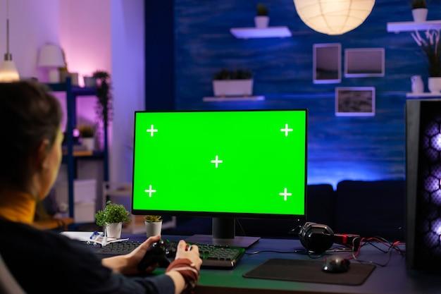 Wettbewerbsfähiger spieler, der einen leistungsstarken pc mit greenscreen-display sucht, der online-spiele für live-turniere spielt. cyber-player, der einen pc mit mock-up-chroma-isolierten desktop-streaming-shooter-spielen verwendet