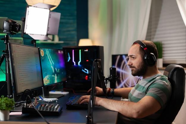 Wettbewerbsfähiges spieler-streaming-esport-turnier mit drahtlosem technologienetzwerk wettbewerbsfähige frau, die einen online-weltraum-shooter-wettbewerb auf einem leistungsstarken professionellen computer spielt und in ein mikrofon spricht