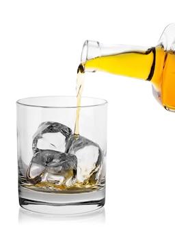 Whiskey aus der flasche mit eis in ein glas gießen