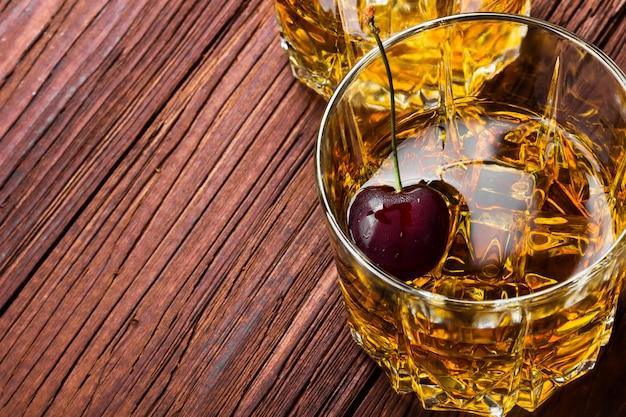 Whiskey mit eis und kirsche in zwei gläsern