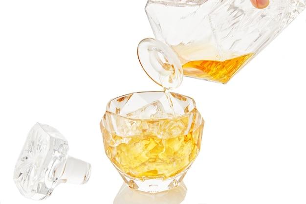 Whisky aus dekanter wird in glas whisky mit eis auf weißem hintergrund mit reflexion gegossen.