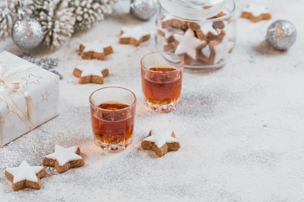 Whisky, brandy oder schnaps, kekse und weihnachtsdekorationen auf weißem hintergrund