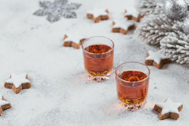 Whisky, brandy oder schnaps, kekse und winterferiendekorationen auf weiß