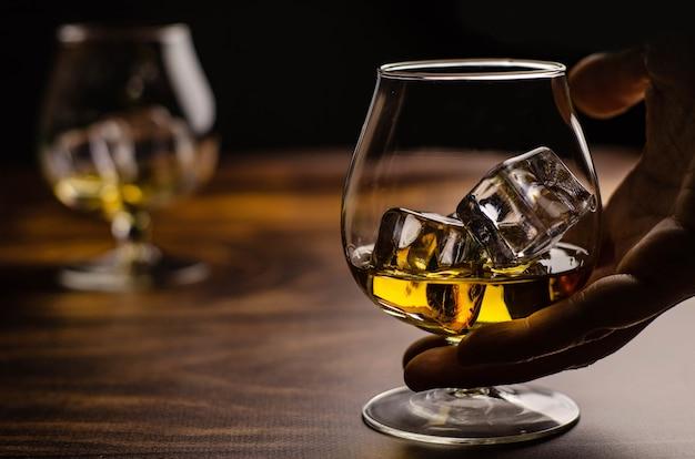 Whisky / cognac-glas mit eis in einer hand auf holz