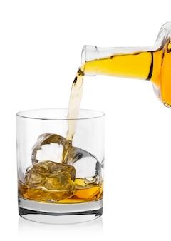 Whisky gießt aus der flasche in rundes glas mit eis
