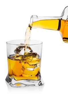 Whisky gießt aus der flasche in transparentes glas mit rundem eis cu