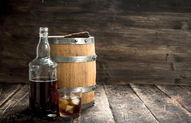 Whisky hintergrund. ein fass scotch whisky mit glas und einer zigarre. auf einem hölzernen hintergrund.