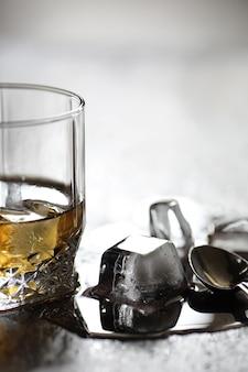Whisky im glas und eiswürfel auf einem holztisch