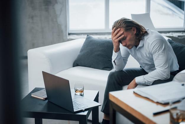Whisky in der nähe des laptops. foto des jungen geschäftsmannes, der auf trainer sitzt und bei der arbeit gestresst wird