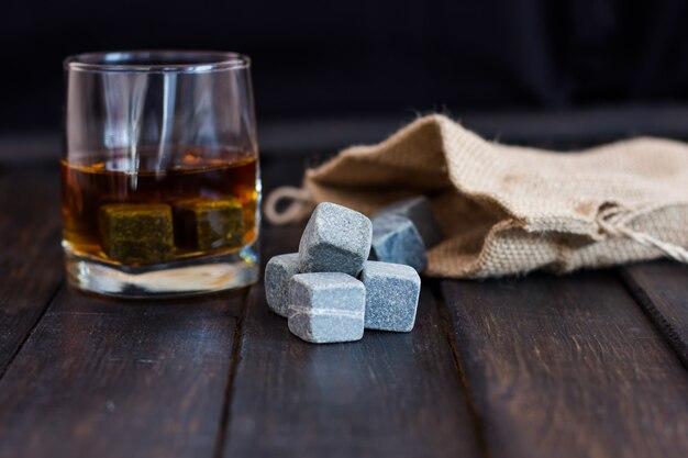 Whisky in einem glas mit steinen für abkühlende getränke auf einem holztisch