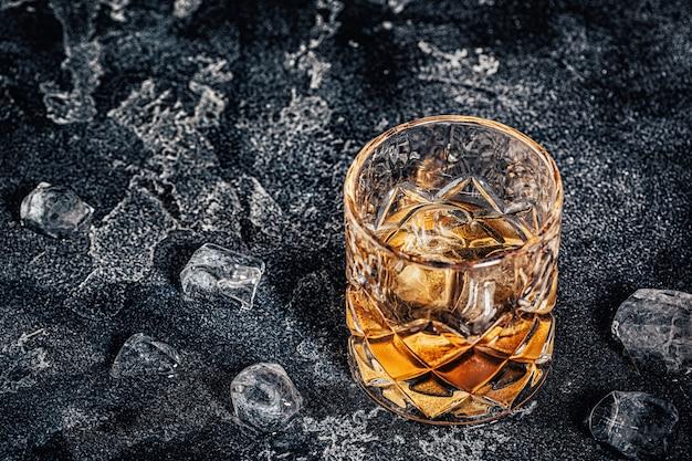 Whisky mit eis auf dunklem steinhintergrund.