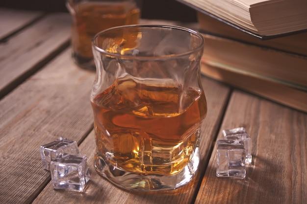 Whisky mit eis auf einem holztisch. in der nähe alte bücher.