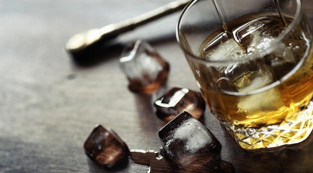 Whisky mit eis mit einem glas. eiswürfel auf einem holztisch und ein glas mit gekühltem starkem alkohol. tisch mit amerikanischem whiskey, bourbon und karten.