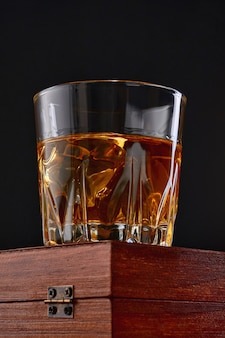 Whisky mit eis oder brandy im glas mit zigarre auf schwarzem tisch. whisky mit eis im glas. whisky oder brandy. selektiver fokus.